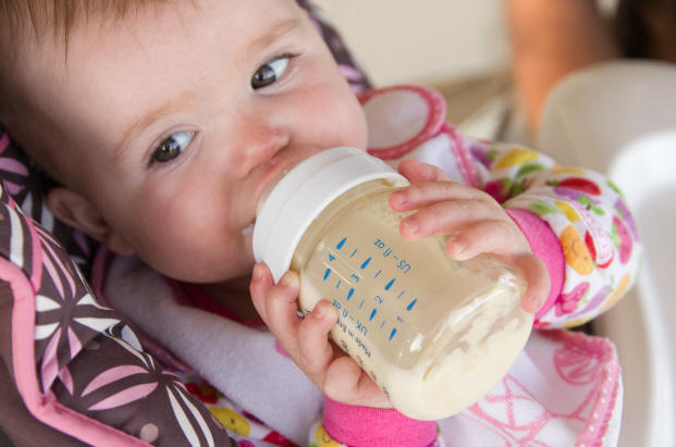 Image of Baby A holding her bottle of milk by Elizabeth Powis Fulks.