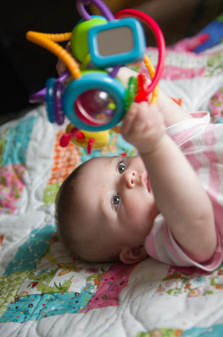 While laying on a quilt, Baby A plays with a colorful toy by Elizabeth Powis Fulks.