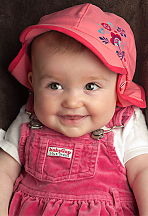 Image of a smiling Baby A in her pink hat and jumper by Elizabeth Powis Fulks.