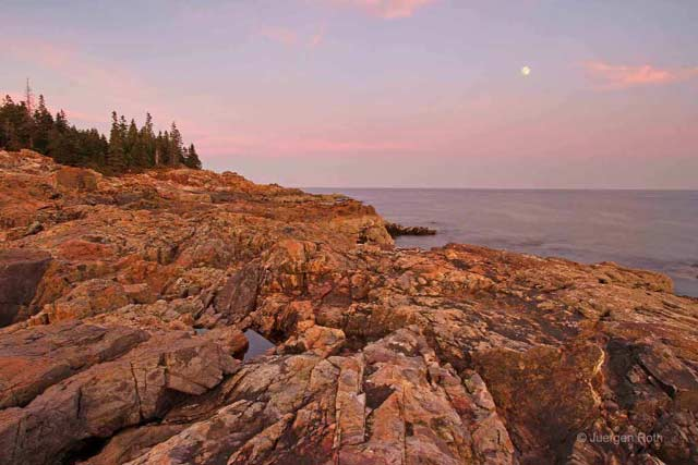 Photo guide to Acadia National Park: Rocky shoreline at sunrise with full moon in the distance by Juergen Roth.