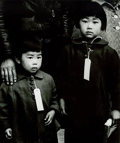 """Enforcement of Executive Order 9066. Japanese Children Made to Wear Identification Tags,"" Hayward, California, 1942, as seen in ""American Masters – Dorothea Lange: Grab a Hunk of Lightning."" Photo Credit: Dorothea Lange, 1942"