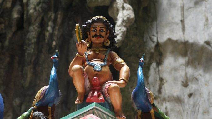 Inside the secondary cave, Hanuman sits atop a temple roof as he stares at the people below.