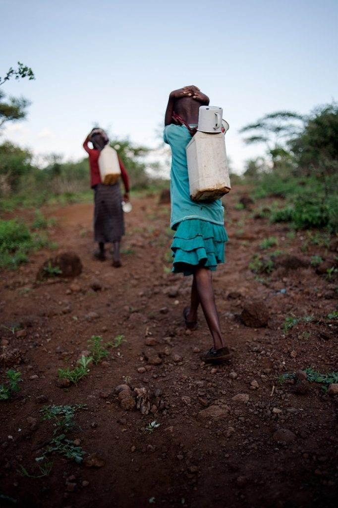 Masai children return from river