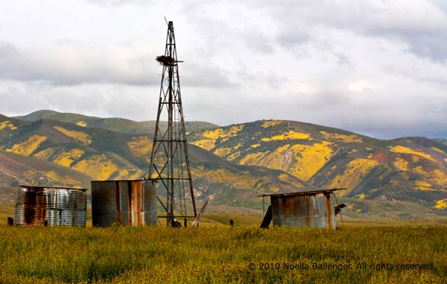 Photo of an old rusted water pump and storage bins on the Carrizo Plains with the Temblor Mountains in the background by Noella Ballenger.