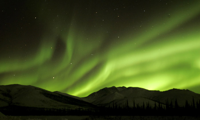 Photo of the Aurora Borealis in bright green with snow covered hills in the foreground in Alaska by Andy Long.