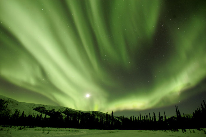 Photo of the Aurora Borealis in greens with snow, hills and trees in foreground and stars in the sky Alaska by Andy Long.