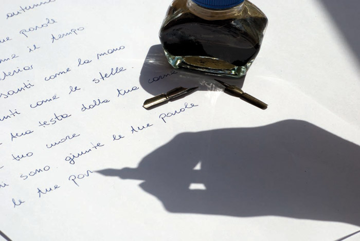 Photo: Ink well and shadow of calligraphy pen in a hand writing textl by Claudia Fiorucci