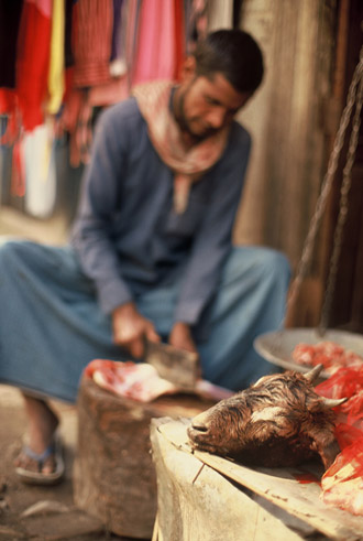 Photo of goat head and butcher in Kashmir, India by Ron Veto