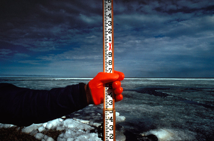Photo of man with bright red glove holding a yardstick at edge of an ice-covered seaside at Prudhoe Bay in Alaska by Gert Wagner