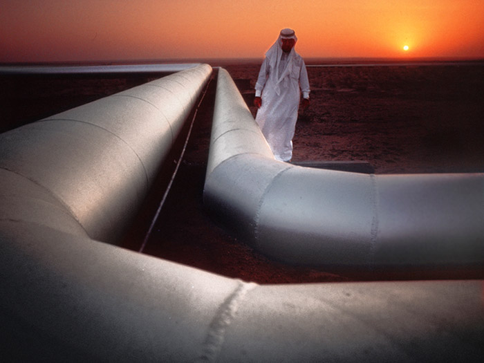Photo of man walking along an oil pipeline at sunset in Emirates by Gert Wagner