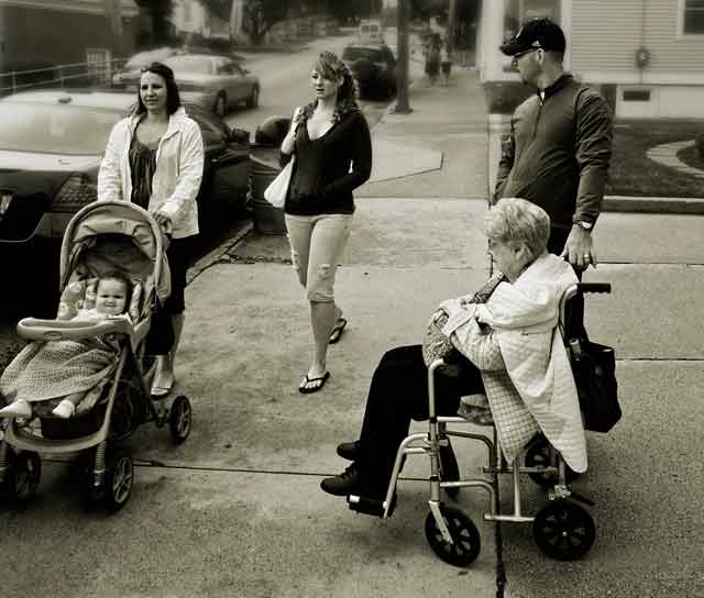 Black and White Inspired Photography: street photo of baby and elderly woman - both in carriers with wheels by Jim Austin.