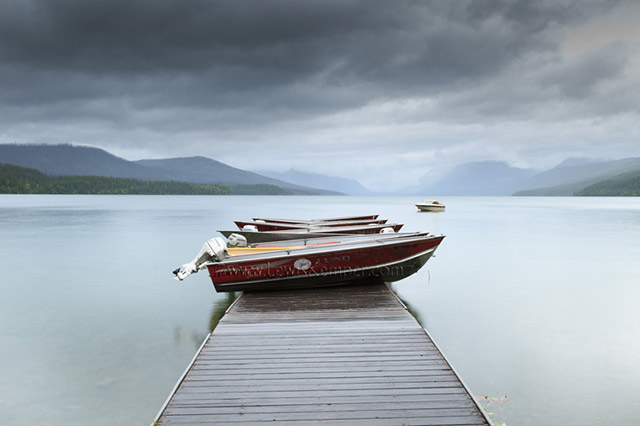 Landscape image of small boats stored up on a dock on a lake in Montana by Lewis Kemper.