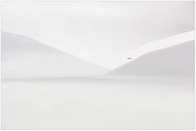 Photographing the Immaterial: gray scale image of rolling hills covered in snow with a single tree entitled There by Piero Leonardi.