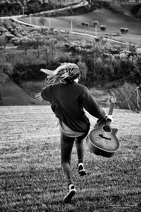 Black and white image of a girl anda her guitar titled Wind of Freedom by Antonio Borzillo.