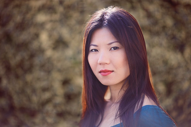 Environmental colored portrait of Asian woman outside by Alex Lagarejos.