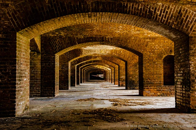 Photo of the red brick structure and arches inside Fort Jefferson, Dry Tortugas National Park, Key West, Florida by William Canosa.