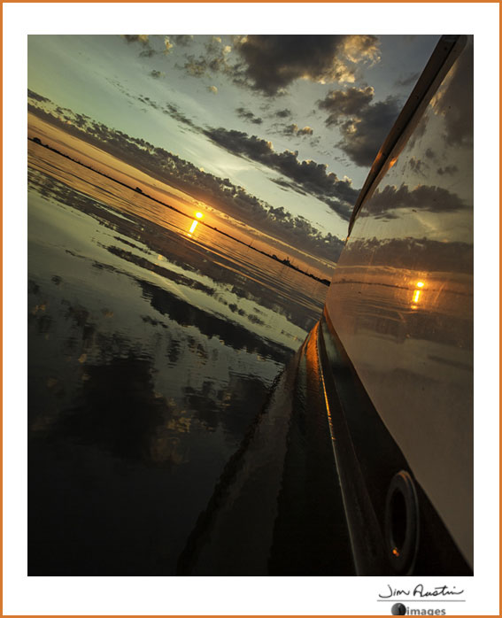 Angled photo of boat and sunrise by Jim Austin