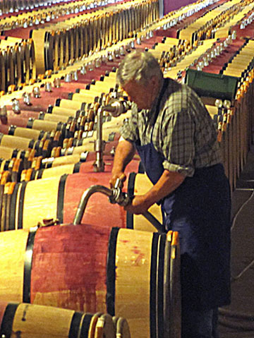 Photo of worker at Chateau Margaux racking the barrels in Southern France by Cliff Kolber