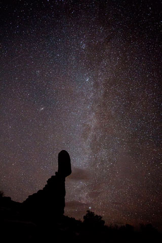 Star photography: stars over silhouetted Balanced Rock at Arches National Park, Utah by Andy Long.
