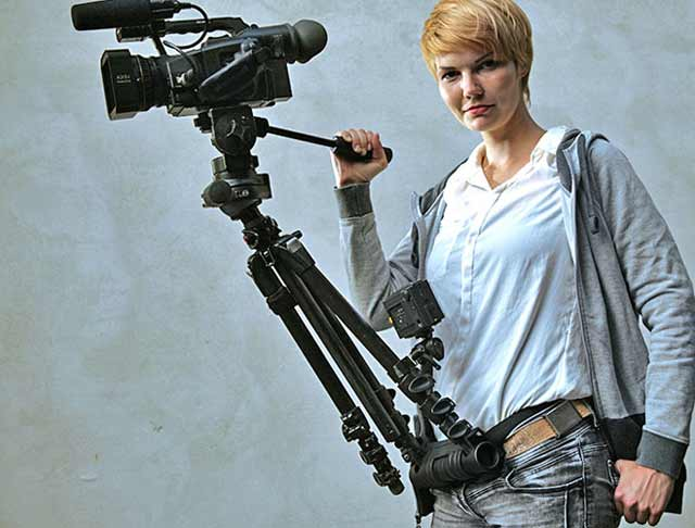 Product Review of hipjib. Close-up of woman with hipjib around her waist that holds a tripod and video camera.