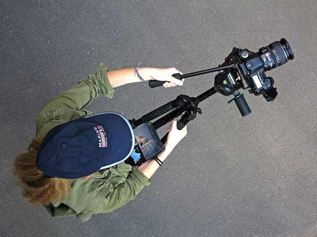 Product Review of hipjib. Top view of a woman with hipjib around her waist holding a tripod with small monitor mounted and video camera.