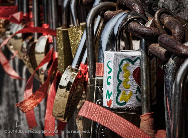 """""""Remnants at the Wall"""": Close-up of love padlocks attached to a chain along a wall at the Great Wall of China by Jean Lua."""