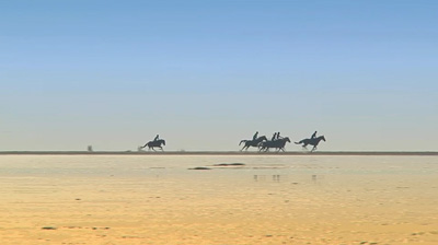 Photo of running horses and riders on beach by Gert Wagner