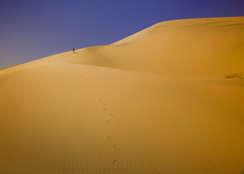 Photo of sand dune, man and footprints in sand at Eureka Valley Sand Dunes at Death Valley National Park by Michael Leggero.