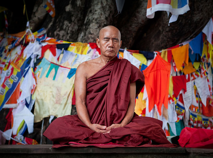 Photo of Buddhist monk meditating in front of fig tree swathed in prayer flags at Mahabodhi Temple, Bodhgaya, India by Nico DeBarmore.