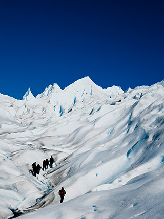 Landscape Photography Mistake and Solution: Hikers on mountain snow with too much blank sky showing by Michael Leggero.