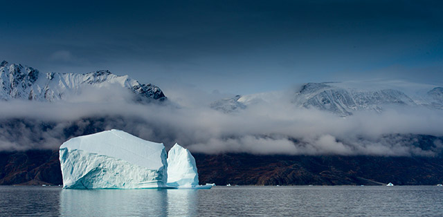 Landscape Photography Mistake and Solution: Iceberg and mountains in the clouds taken with ISO 1000 by Michael Leggero.