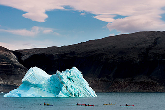Landscape Photography Mistake and Solution: Iceberg and kayakers on lake taken with zoom lens by Michael Leggero.