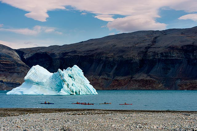 Landscape Photography Mistake and Solution: Iceberg and kayakers on lake taken with wide angle lens by Michael Leggero.
