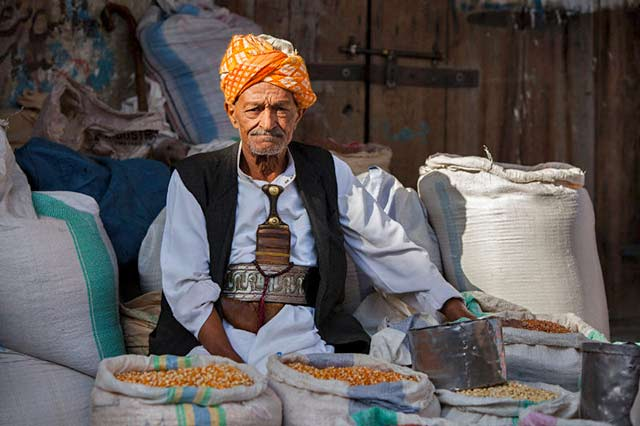 Yemeni clothing: Man wearing traditional dress, shawl and dagger sells grain at a market by Maarten de Wolf.