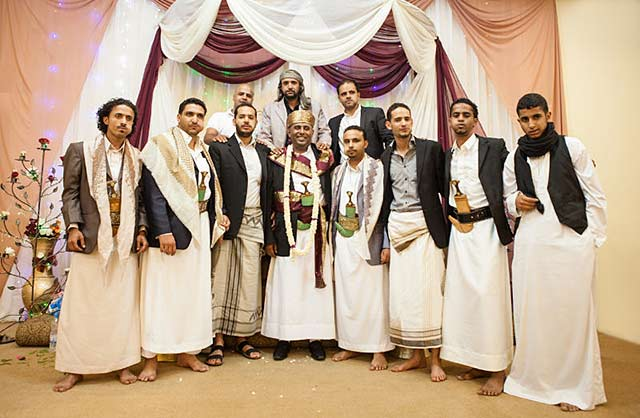 Yemeni clothing: Men wearing traditional thoobs and ma'wazz at a wedding by Maarten de Wolf.