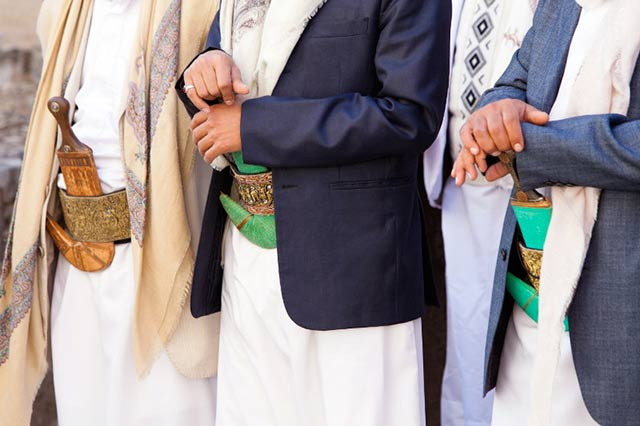 Yemeni clothing: Close-up of men wearing thoobs and resting their hands on their jambiyya (daggers) by Maarten de Wolf.