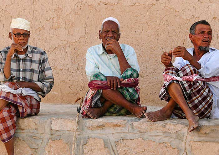 Yemeni clothing: Men in traditional plaid futa's sitting on a rock wall by Maarten de Wolf.