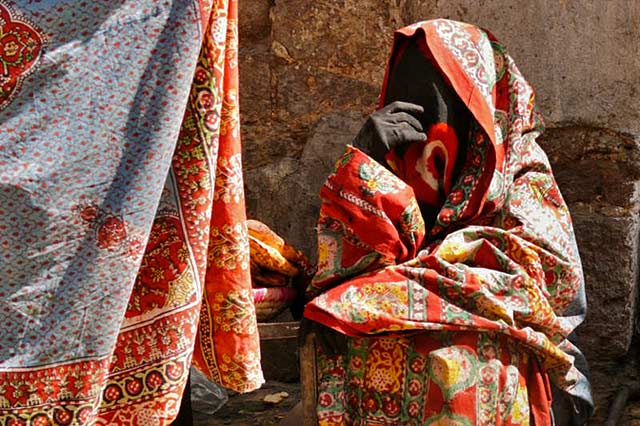 Yemeni clothing: A woman in a colorful printed sitara at the market by Maarten de Wolf.