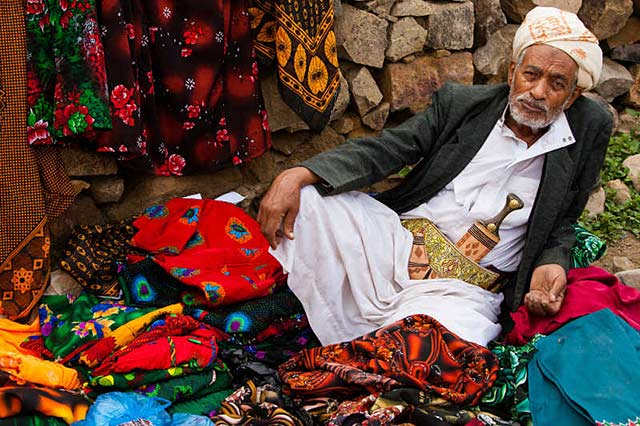 Yemeni clothing: Man wearing traditional dress, shawl and dagger sells women's clothes in the countryside by Maarten de Wolf.