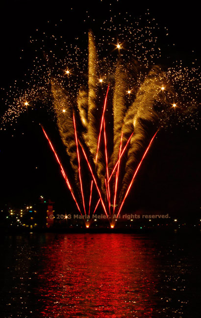 Red and gold, stripes, squiggels and star fireworks reflected in the river by Marla Meier.
