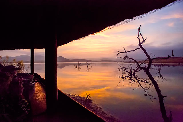 Photographers creating sunset photos of a dam from a l odge in South Africa by Noella Ballenger.