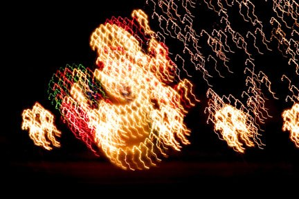 Photo of Christmas lights made while bobble and weaving the camera on a santa display by Noella Ballenger.