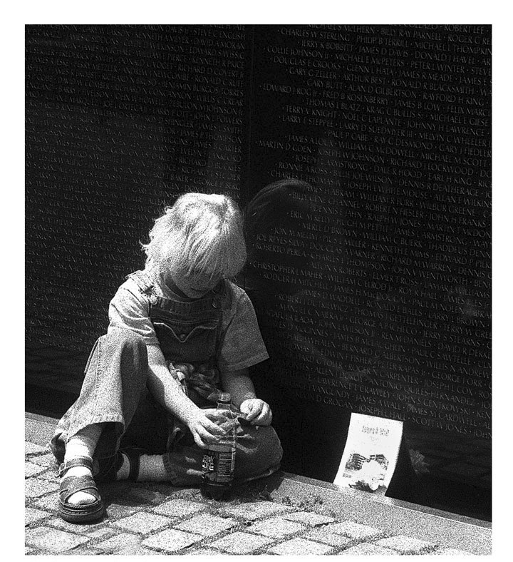 Photo of a little boy with a drink bottle at a memorial wall called Thirst by Jim Austin