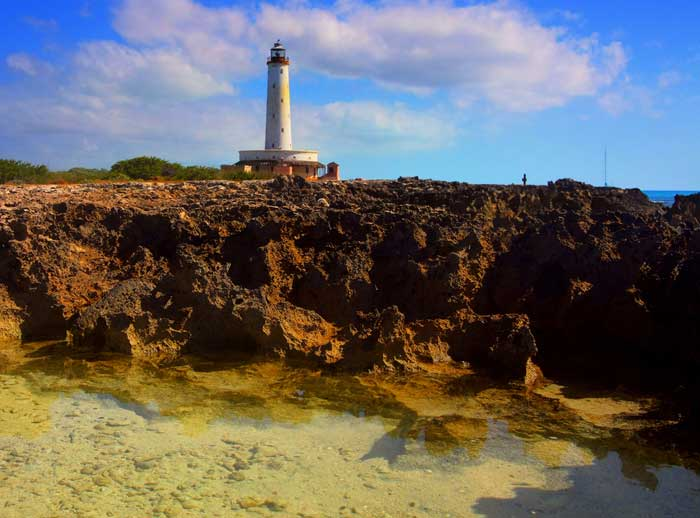 HDR image of rocky shores and Bird Rock Cay Lighthouse on Crooked Island, Bahamas by Jim Austin.