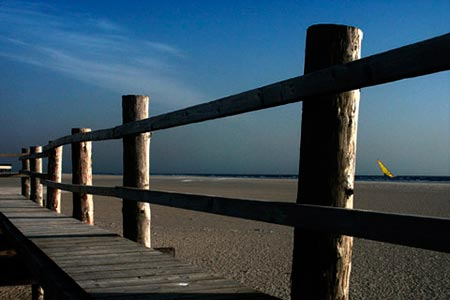 Photo showing depth: Dominant boardwalk in foreground with beach and sea in background by Gert Wagner.