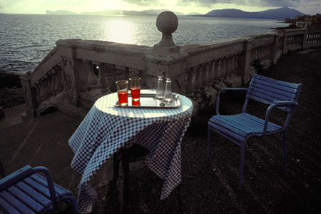 Photo horizons: image of cafe table and chairs on patio overlooking the sea by Gert Wagner