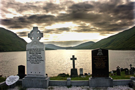Photo showing depth: cemetery in foreground with sea and mountains in background by Gert Wagner.