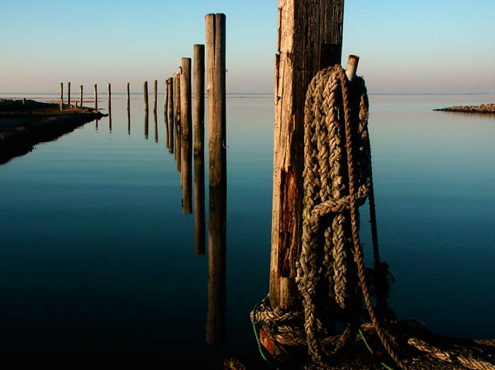 Photo of a seaside port depicting distant horizon line and importance of foreground subject in a scene by Gert Wagner
