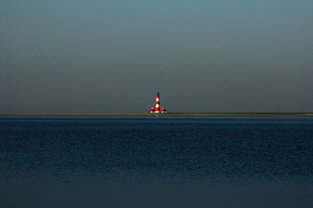 Photo showing centered horizon linet: image of sea and land with a red and white striped lighthouse by Gert Wagner