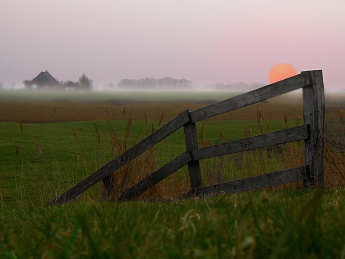 Photo of scene taken with a telephoto lens: fence in foreground and sunset in background by Gert Wagner.